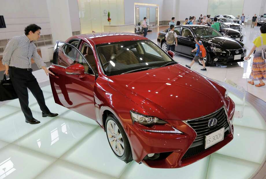 A visitor looks at a Lexus IS300h displayed at Toyota Motor Corp.'s showroom Toyota Mega Web in Tokyo Friday, Aug. 2, 2013. Toyota nearly doubled its April-June profit from a year ago to 562.1 billion yen ($5.5 billion), getting a big boost from a cheap yen. Photo: Itsuo Inouye