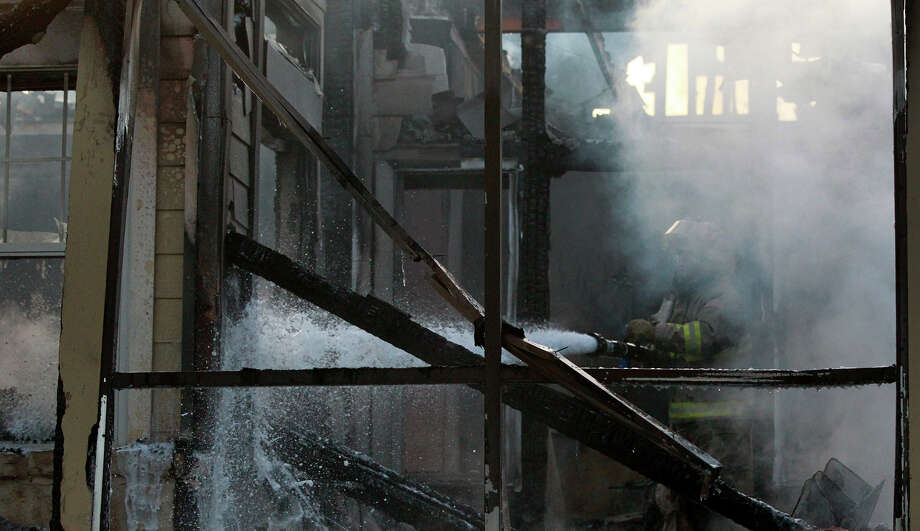A San Antonio firefighter hoses down a burned unit of a duplex that caught on fire about 6:00 a.m. Friday August 2, 2013 at the Independence Village at Stone Oak homes on the 20,000 block of Huebner Road. Battalion Chief Brooke Hildreth said there was about $200,000 in damage to the structure and contents of the building and there were no injuries. Photo: JOHN DAVENPORT, SAN ANTONIO EXPRESS-NEWS / ©San Antonio Express-News/Photo may be sold to the public