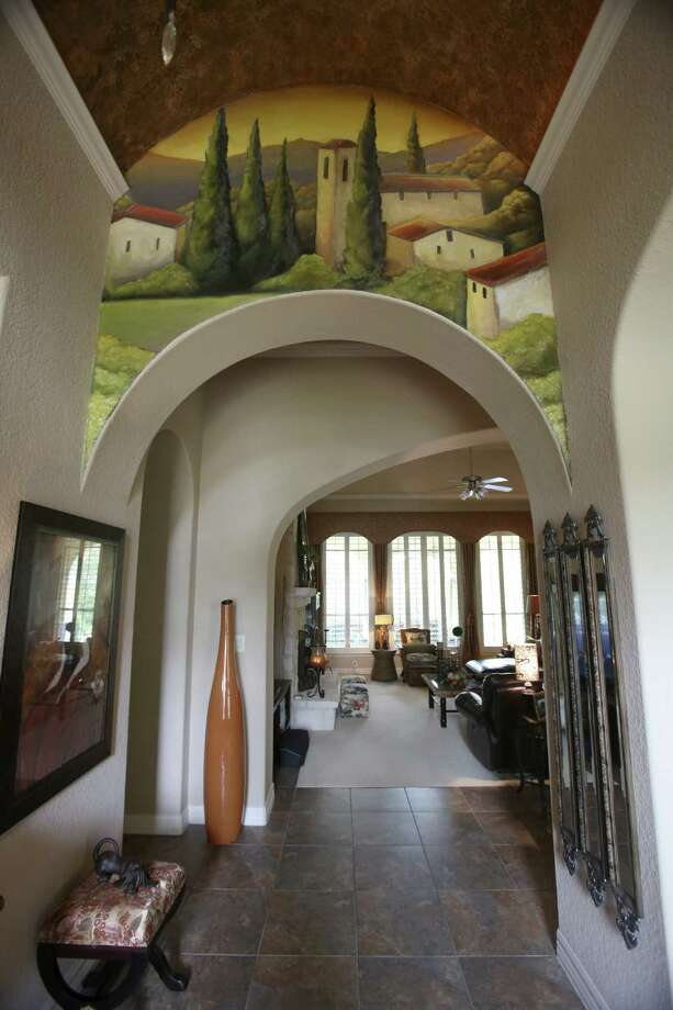 A Tuscan village mural painted in the entry foyer is one of several murals Iris Mayer commissioned for her Stone Oak home. Photo: Photos By Helen L. Montoya / San Antonio Express-News