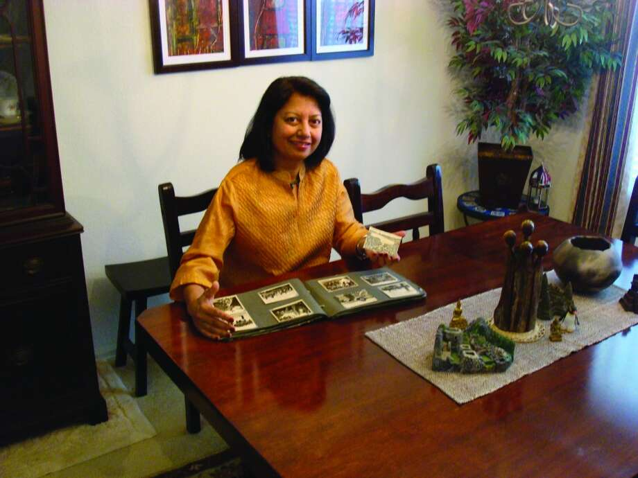 Dr. Sandy Rao, a professor and graduate studies advisor at Texas State University in San Marcos, looks through her family photo album. Her father's old black-and-white photo of his trip to Zurich inspired her to retrace some of his steps in the historic city. Photo: Peter Dusan, For The Express-News