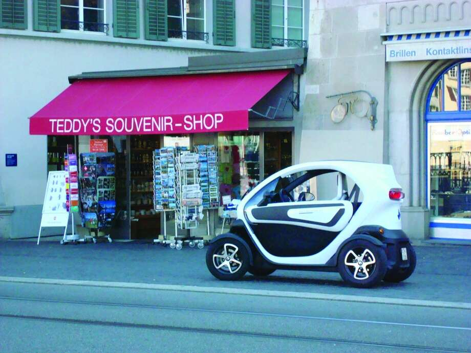 A tiny Renault Twizy provides handy and inexpensive transportation for a woman parked at a souvenir shop. Photo: Sandy Rao, For The Express-News