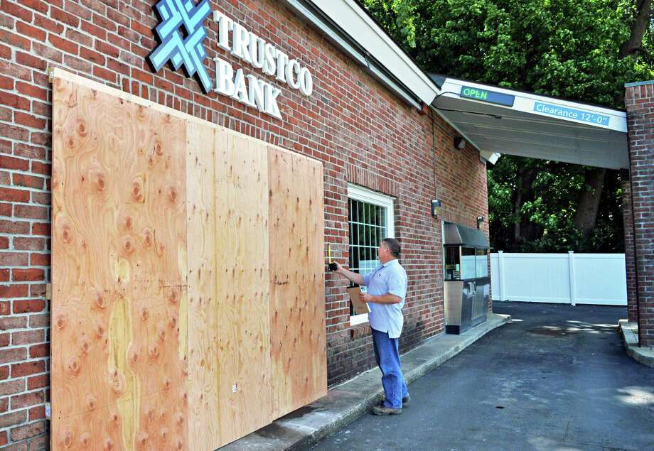 Contractor Jeff Quay of Rotterdam assesses the damage Friday, Aug. 2, 2013, where an SUV crashed into a Trustco bank branch in Rotterdam on Thursday near the intersection of Curry Road and Altamont Avenue in Rotterdam, N.Y. (John Carl D'Annibale / Times Union) Photo: John Carl D'Annibale
