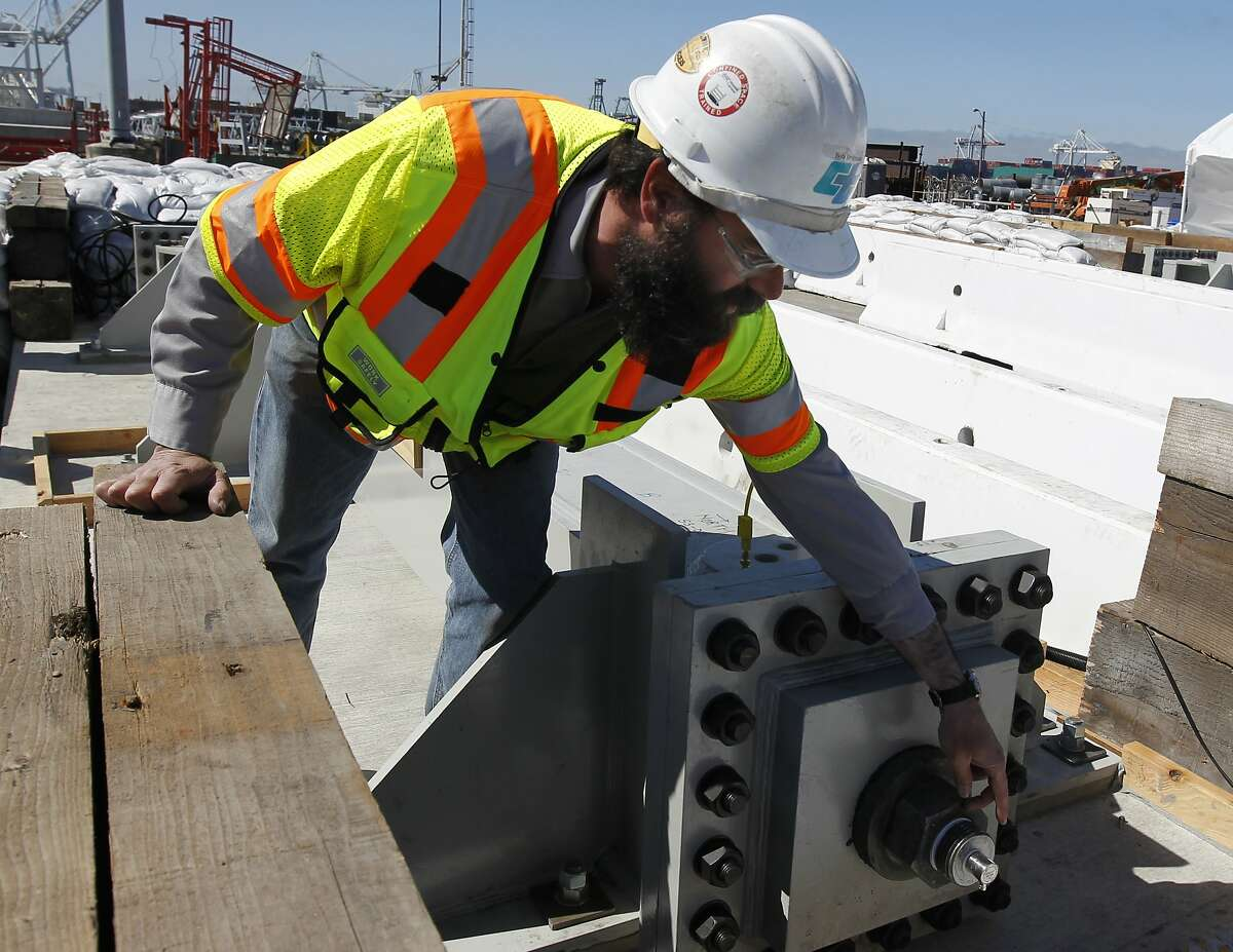 Engineer Bob Brignano examines the exposed end of on anchor rod cast in 2010 undergoing a corrosion stress test for the new eastern span of the Bay Bridge in Oakland, Calif. on Friday, Aug. 2, 2013. The accelerated test, lasting 23 days, simulates long-term exposure to a salt water environment.