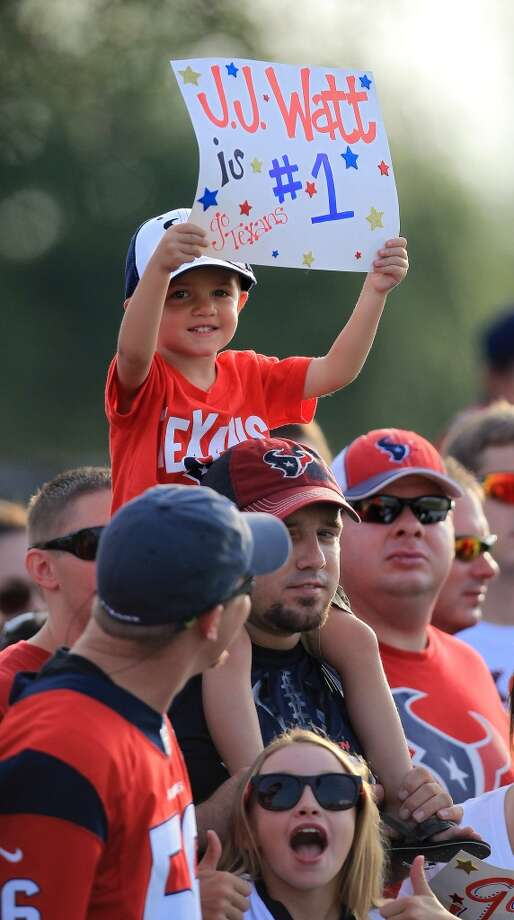 Connor Wakefield, 3, of Texas City, holds up a sign for J.J. Watt while he sits on the shoulder of his dad, Ricky, as they watch players during camp on Friday. Photo: Karen Warren, Chronicle