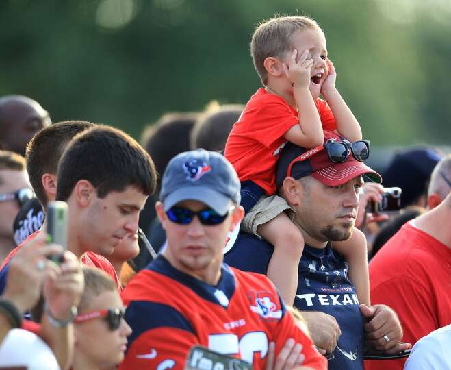Connor Wakefield, 3, of Texas City, sits on the shoulder of his dad, Ricky, as they watch players du