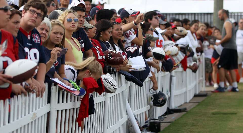 Fans line up as the wait for Texans players to sign autographs for them.