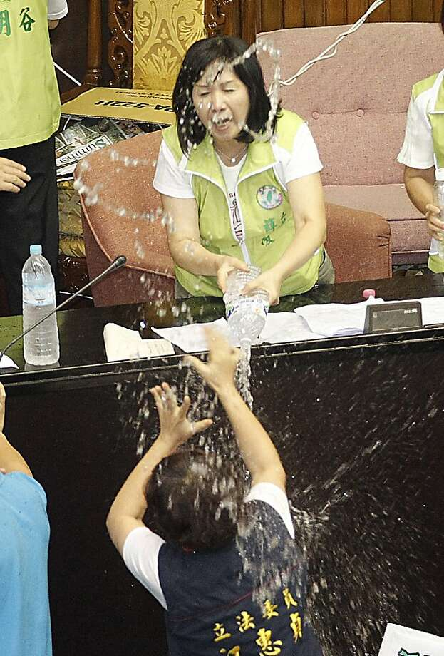 Good thing these people aren't armed: An opposition lawmaker douses a ruling lawmaker with water during a spirited debate over 