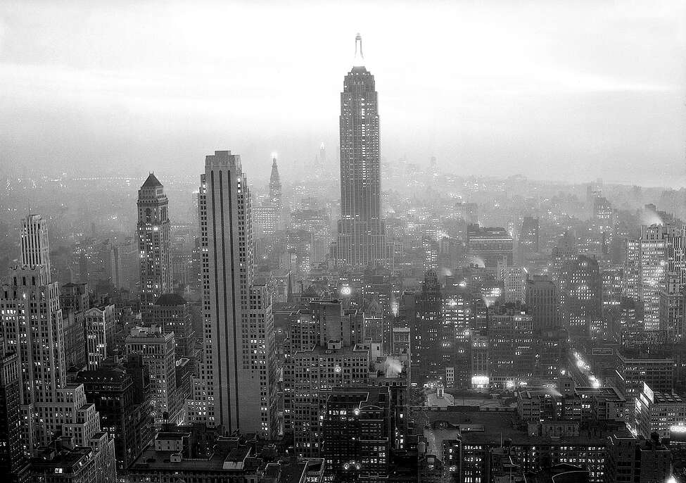 As Autumn dusk creeps slowly over New York City, the variegated electric displays of the skyscrapers pierce the twilight for miles. This photograph, taken Oct. 13, 1932 from the rapidly rising $250,000,000 Rockefeller Center, shows the Empire State Building dominating the scene. In the left center glows the single light atop the Metropolitan Tower and in the foreground stands the building at 500 Fifth Avenue.