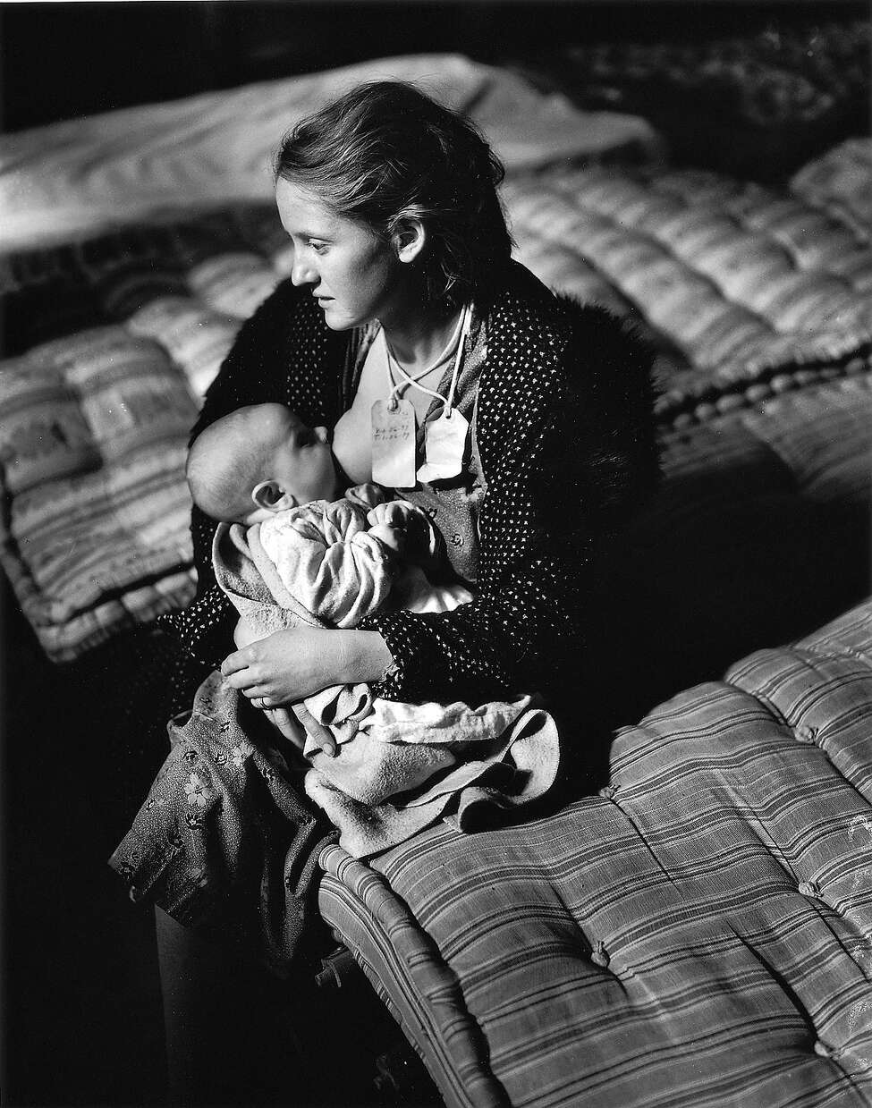 Mrs. Winifred Waver and her baby son, Charles, refugees of flooded Luxora, Ark., wait at a Memphis, Tenn., refugee camp for floodwaters to subside Jan. 29, 1937. The tags on their necks provide identification.