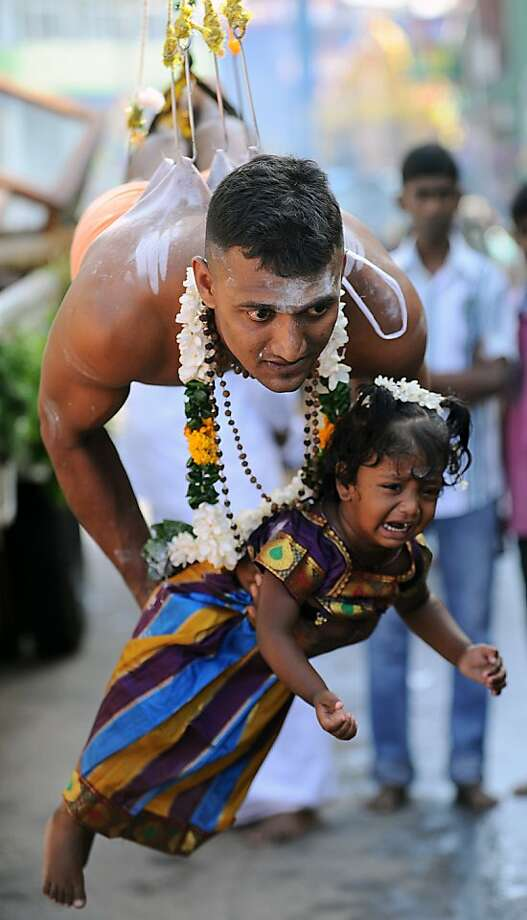 Baited hooks: A Tamil Hindu suspended by hooks piercing his back holds an understandably upset little girl during the Vel Hinduism festival in Colombo, Sri Lanka. Photo: Ishara S.Kodikara, AFP/Getty Images