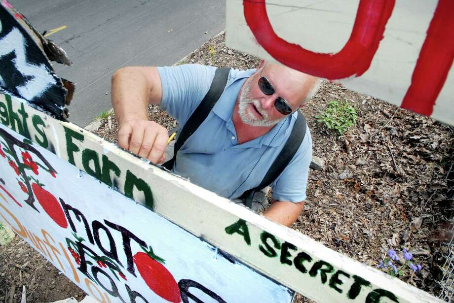 Farmer Randy Brown paints the sign at the entrance to Hubbard Heights Farm in Stamford, Conn. on Friday August 2, 2013. Photo: Dru Nadler / Stamford Advocate Freelance