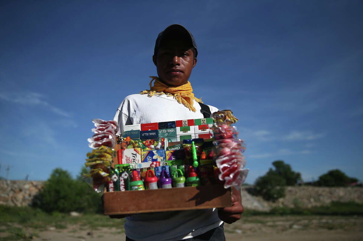Jorge Hernandez from Guatemala sells candy and cigarettes on the Mexican side of the Suchiate River from Mexico into Guatemala on August 2, 2013 in Ciudad Hidalgo, Chiapas, Mexico. Thousands of undocumeted Central Americans pass illegally into Mexico across the river, many of them immigrants on the first leg of their long and perilous journey north to the United States.