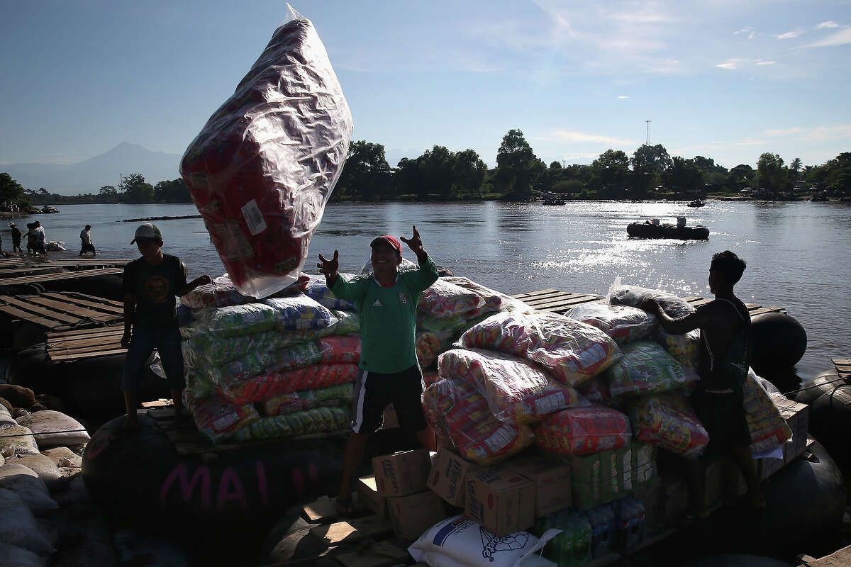 Merchandise is loaded onto a raft to cross the Suchiate River from Mexico into Guatemala on August 2, 2013 in Ciudad Hidalgo, Chiapas, Mexico. Commerce passes each way on the river, to avoid customs duties. Meanwhile, thousands of undocumeted Central Americans also pass illegally into Mexico across the same river, many of them immigrants on the first leg of their long and perilous journey north to the United States.