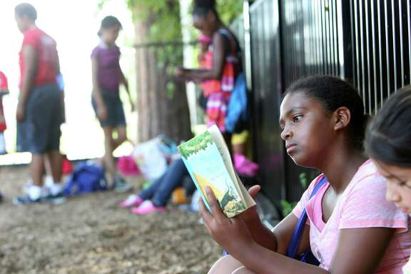 Tiffany Scott, 10, reads a book during summer camp at Foster YMCA.