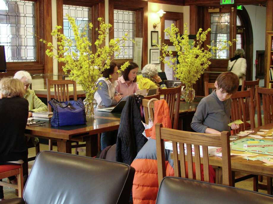 The reading room at the Pequot Library had vases of forsythia on tables when this photo was take in April. Under a new schedule announced Friday, the Southport landmark will reduce its hours by one hour a day on weekdays and by one or two hours on Saturdays, depending on the time of year. Photo: Contributed Photo / Fairfield Citizen