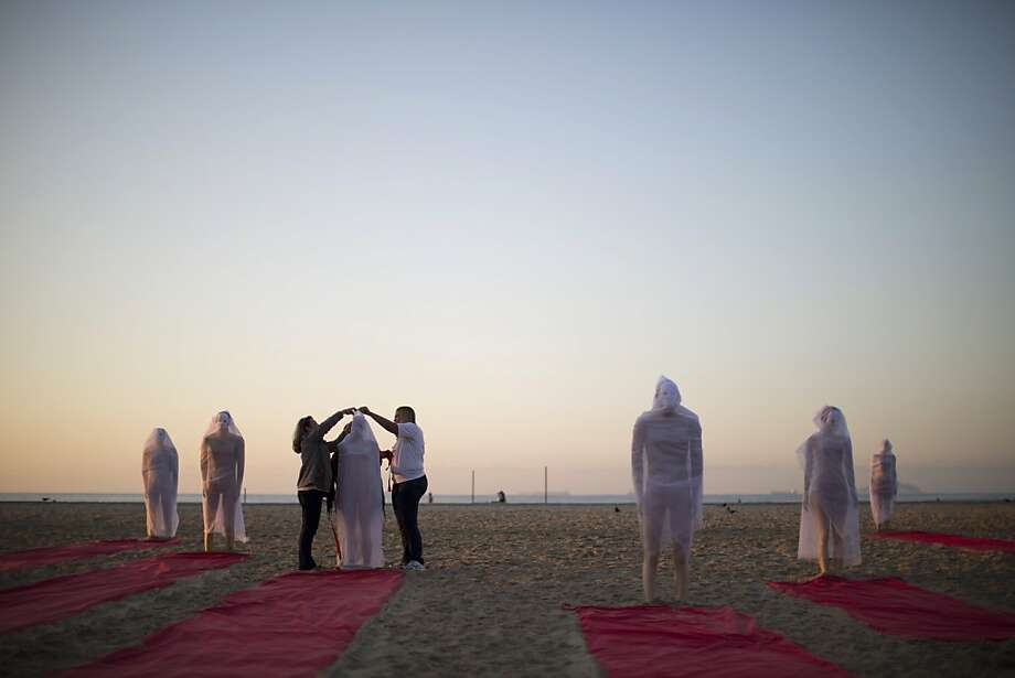 A girl holds a candle, above, and Rio de Paz activists, right, wrap a mannequin in a veil on a beach at protests over thousands of missing persons. Photo: Felipe Dana, Associated Press