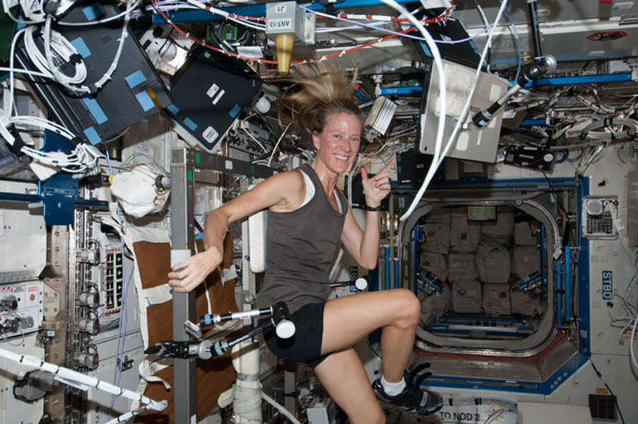 NASA astronaut Karen Nyberg, Expedition 36 flight engineer, poses for a photo while exercising on the Cycle Ergometer  in the Destiny laboratory of the International Space Station.