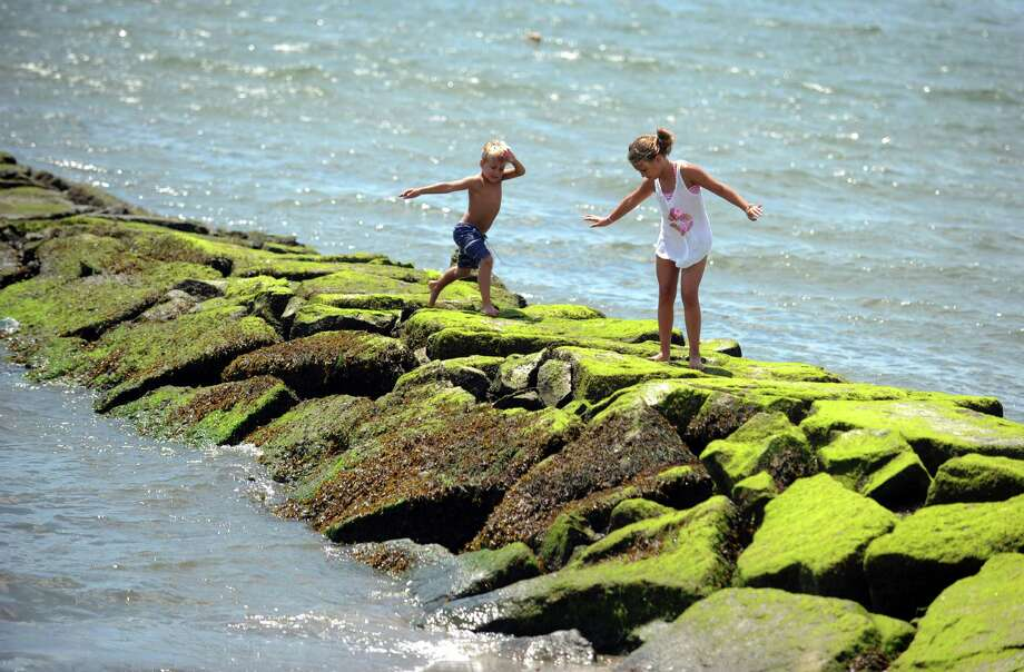 Six-year-old Wesley Feher, of Fairfield, and his sister Bella, 10, leap along the jetty at Sasco Beach in Fairfield, Conn. Friday, Aug. 2, 2013. Photo: Autumn Driscoll / Connecticut Post