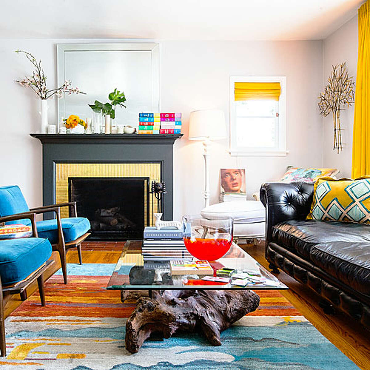 Same colors, different ways O'Brien and Leaver used many of the same hues in both their kitchen and living room. Here in the living room, teal dominates, while charcoal gives the fireplace more heft. Patches of hot yellow in the rug encouraged the couple to hang curtains in the same shade.