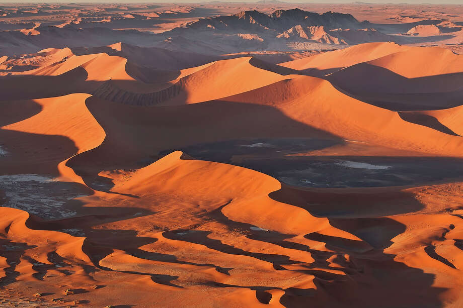"""Namibia: Namib Sand Sea""""Namib Sand Seais the only coastal desert in the world that includes  extensive dune fields influenced by fog. Covering an area of over three  million hectares and a buffer zone of 899,500 hectares, the site is  composed of two dune systems, an ancient semi-consolidated one overlain  by a younger active one. The desert dunes are formed by the  transportation of materials thousands of kilometres from the hinterland,  that are carried by river, ocean current and wind. It features gravel  plains, coastal flats, rocky hills, inselbergs within the sand sea, a  coastal lagoon and ephemeral rivers, resulting in a landscape of  exceptional beauty. Fog is the primary source of water in the site,  accounting for a unique environment in which endemic invertebrates,  reptiles and mammals adapt to an ever-changing variety of microhabitats  and ecological niches."""" — UNESCO Photo: Werner Van Steen, Getty Images / (c) Werner Van Steen"""