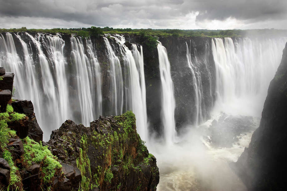 """Zambia/Zimbabwe: Mosi-oa-Tunya / Victoria Falls""""These are among the most spectacular waterfalls in the world. The  Zambezi River, which is more than 2 km wide at this point, plunges  noisily down a series of basalt gorges and raises an iridescent mist  that can be seen more than 20 km away."""" — UNESCO Photo: JoSon, Getty Images / (c) joSon"""