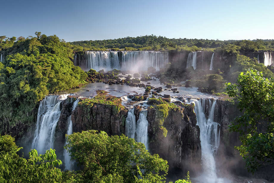 """Argentina: Iguazu National Park""""The semicircular waterfall at the heart of this site is some 80 m high  and 2,700 m in diameter and is situated on a basaltic line spanning the  border between Argentina and Brazil. Made up of many cascades producing  vast sprays of water, it is one of the most spectacular waterfalls in  the world. The surrounding subtropical rainforest has over 2,000 species  of vascular plants and is home to the typical wildlife of the region:  tapirs, giant anteaters, howler monkeys, ocelots, jaguars and caymans."""" — UNESCO Photo: Roevin, Getty Images/Flickr Open / Flickr Open"""