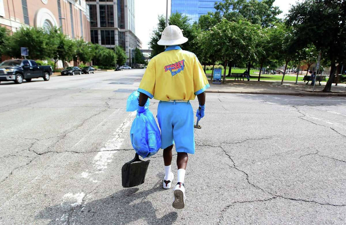 Alvin Ross, a member of the Downtown Management District's Street Team, carries a garbage bag as he looks for litter downtown.