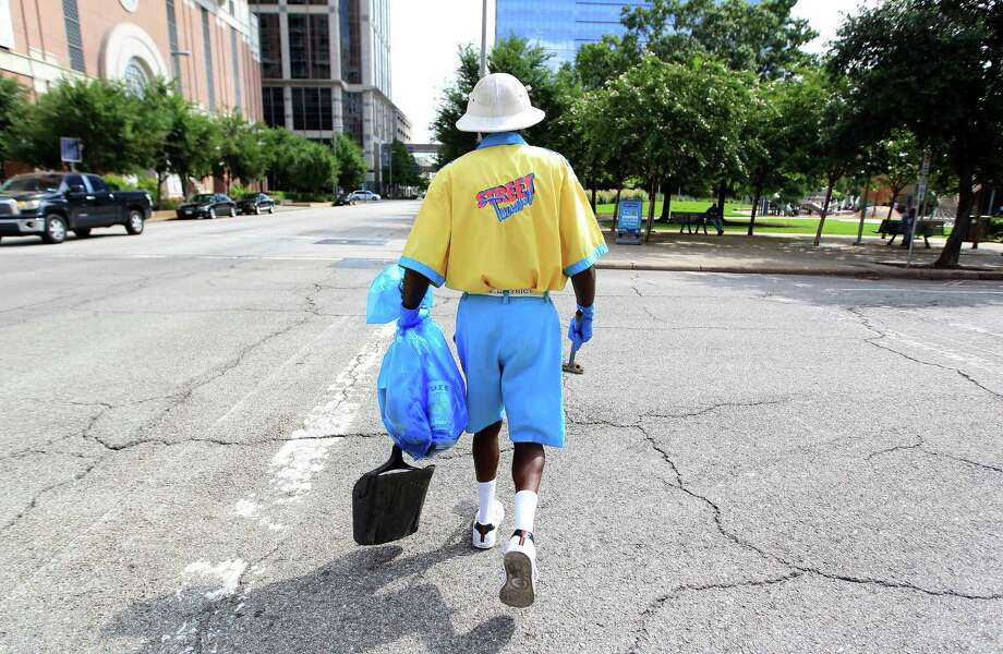 Alvin Ross, a member of the Downtown Management District's Street Team, carries a garbage bag as he looks for litter downtown. Photo: Karen Warren, Staff / © 2013 Houston Chronicle