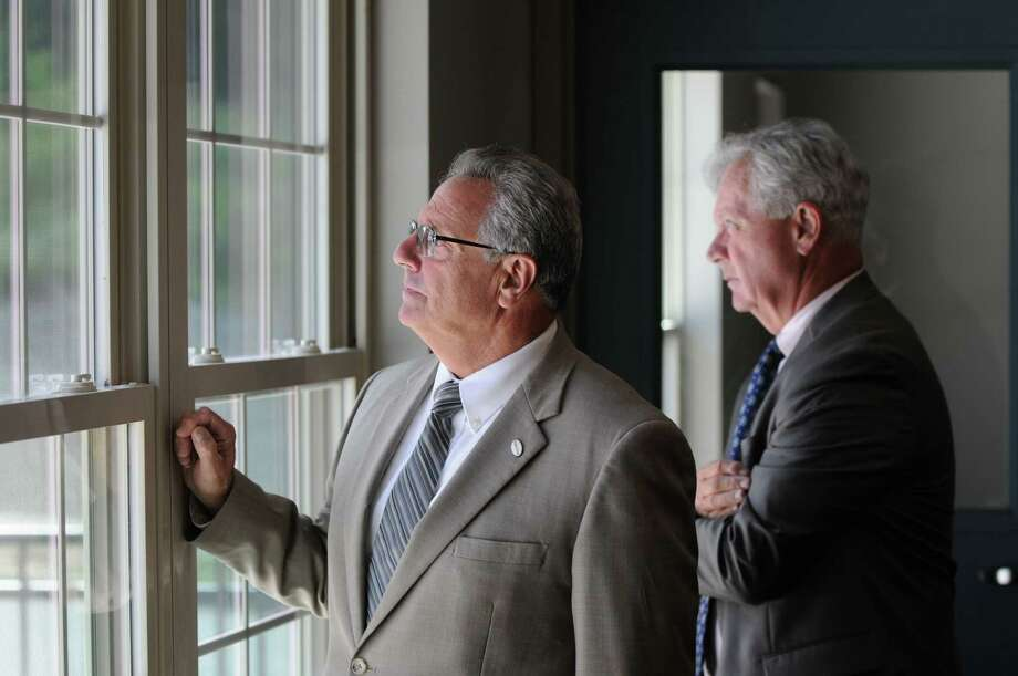 Troy mayor Lou Rosamilia, left, and deputy mayor Peter Ryan, right, peer out of a window at City Station East to admire the landscaping Friday morning, Aug. 2, 2013, during a tour of City Station in Troy, N.Y. (Will Waldron/Times Union) Photo: WW / 10023377A