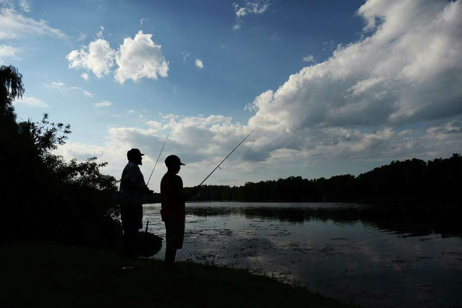 Archie Brinson, left, of Danbury, teaches Domenic Perez, 8, of Danbury, how to fish at Lake Mamanasco in Ridgefield, Conn. on Friday, Aug. 2, 2013. Photo: Tyler Sizemore / The News-Times