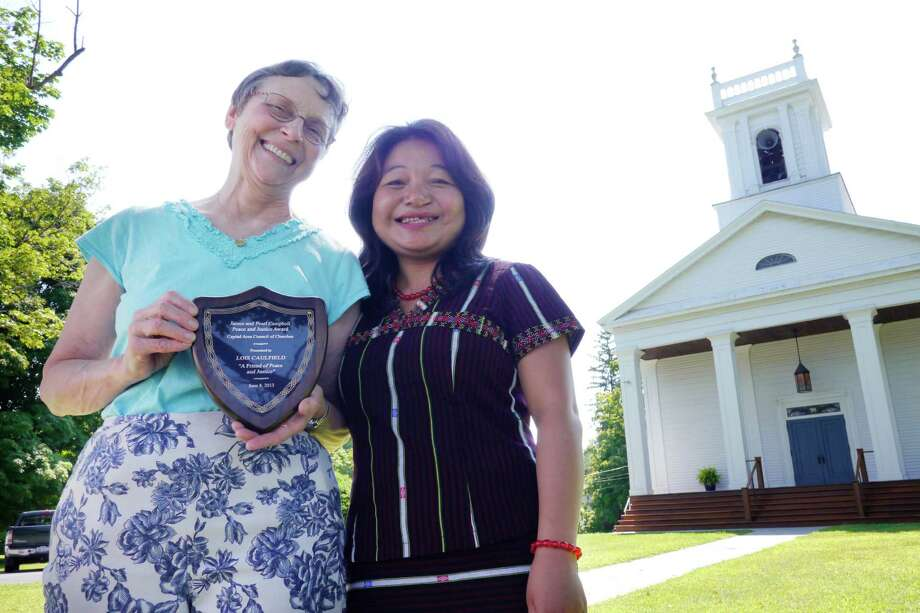 Lois Caulfield, left, poses with Mawi Te, a refugee from Myanmar, right, outside the Delmar Reformed Church Monday, July 29, 2013 in Delmar, N.Y.  Caulfield recently received the Capital Area Council of Churches's James & Pearl Campbell Peace and Justice Award for her work with local immigrants and refugees, like Te.  Te came to Albany with her husband in December of 2012 from a refugee camp in Malaysia.  (Paul Buckowski / Times Union) Photo: Paul Buckowski / 00023301A