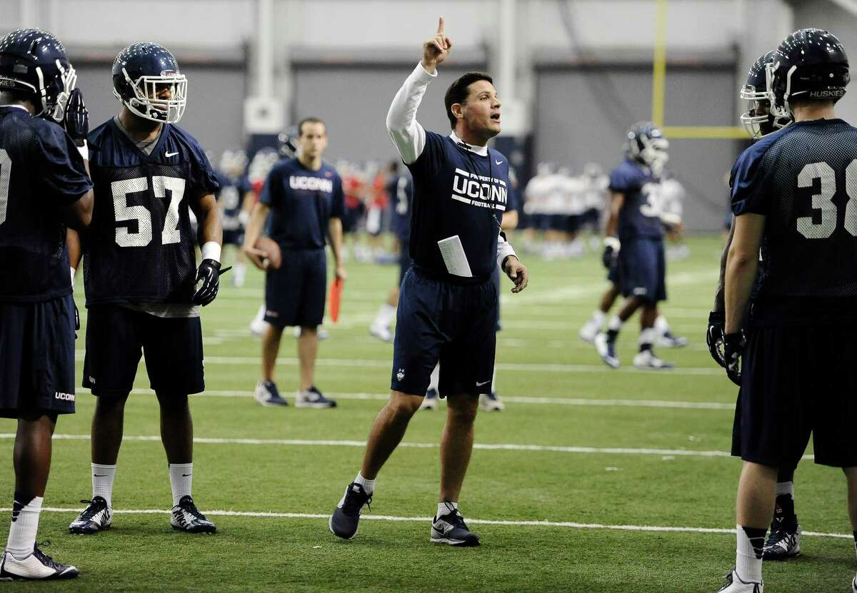 Connecticut head coach Bob Diaco, center talks to his team during the first NCAA college football practice, Saturday, Aug. 2, 2014, in Storrs, Conn. (AP Photo/Jessica Hill)