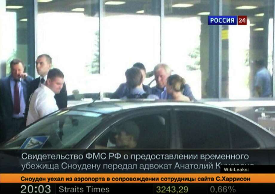 In this still image taken on Thursday, Aug. 1, 2013 and released by Russia24 TV channel, shows Russian lawyer Anatoly Kucherena, second right in the center, and National Security Agency leaker Edward Snowden, center back to a camera, as Snowden leaves Sheremetyevo airport outside Moscow, Russia, on Thursday, Aug. 1, 2013. Snowden has received asylum in Russia for one year and left the transit zone of Moscow's airport, his lawyer said Thursday.  Kucherena said that Snowden's whereabouts will be kept secret for security reasons.  (AP Photo/Russia24 via Associated Press Television) TV OUT ORG XMIT: XAZ101 / Russia24 via Associated Press Television