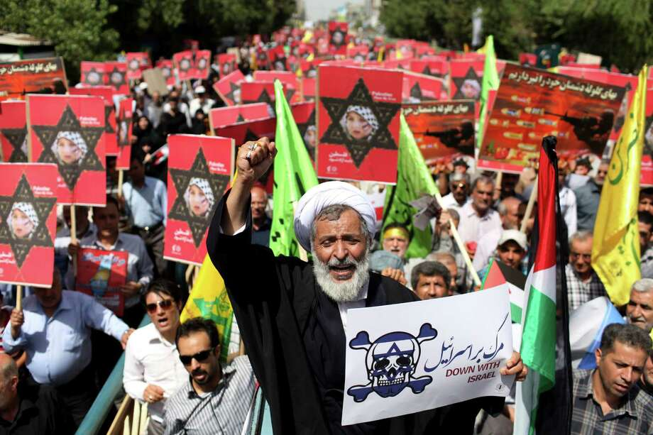 An Iranian cleric holding an anti-Israeli placard chants slogan, while attending an annual pro-Palestinian rally marking Al-Quds (Jerusalem) Day in Tehran, Iran, Friday, Aug. 2, 2013. The last Friday of the Islamic holy month of Ramadan is observed in many Muslim countries as Al-Quds day, as a way of expressing support to the Palestinians and emphasizing the importance of Jerusalem to Muslims.  (AP Photo/Ebrahim Noroozi) ORG XMIT: ENO101 Photo: Ebrahim Noroozi / AP