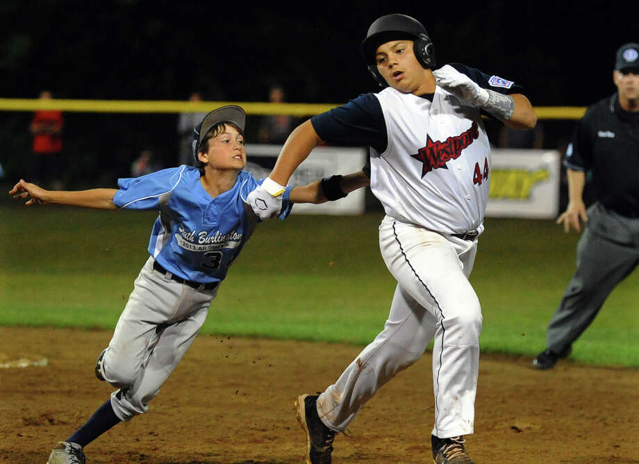 Westport's Matthew Brown gets tagged out in a rundown between first and second by South Burlington's Max Plunkett during Little League Baseball Eastern Regional Tournament action in Bristol, Conn. on Friday August 2, 2013. Brown tied up the opposing team in the rundown allowing a tie breaking run to come in during the third inning making the score 3-2. Photo: Christian Abraham / Connecticut Post