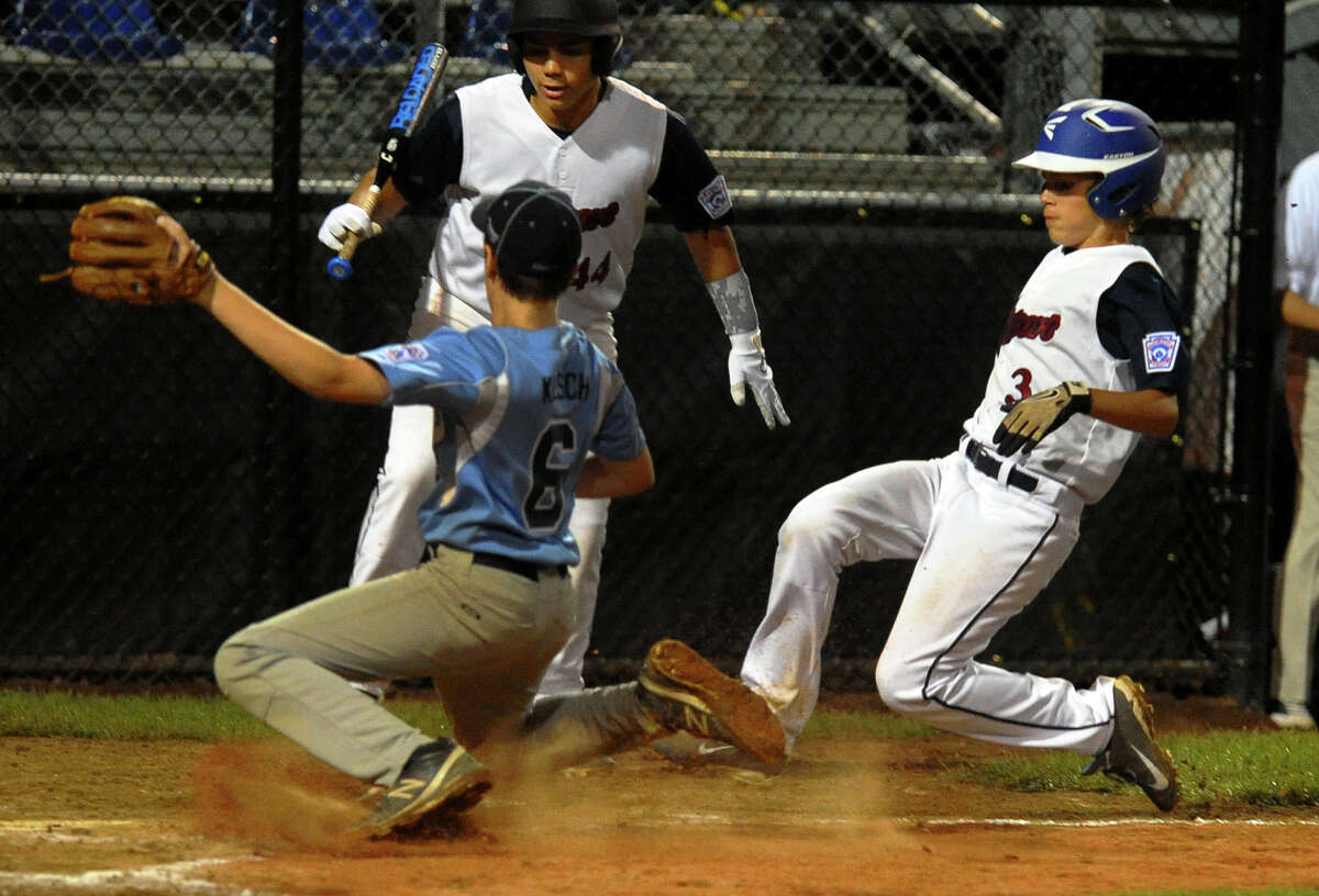 Westport's Max Popken slides into home plate as South Burlington's Ethan Klesch tries to make the tag, during Little League Baseball Eastern Regional Tournament action in Bristol, Conn. on Friday August 2, 2013.Popken was called safe, tying the game 2-2.