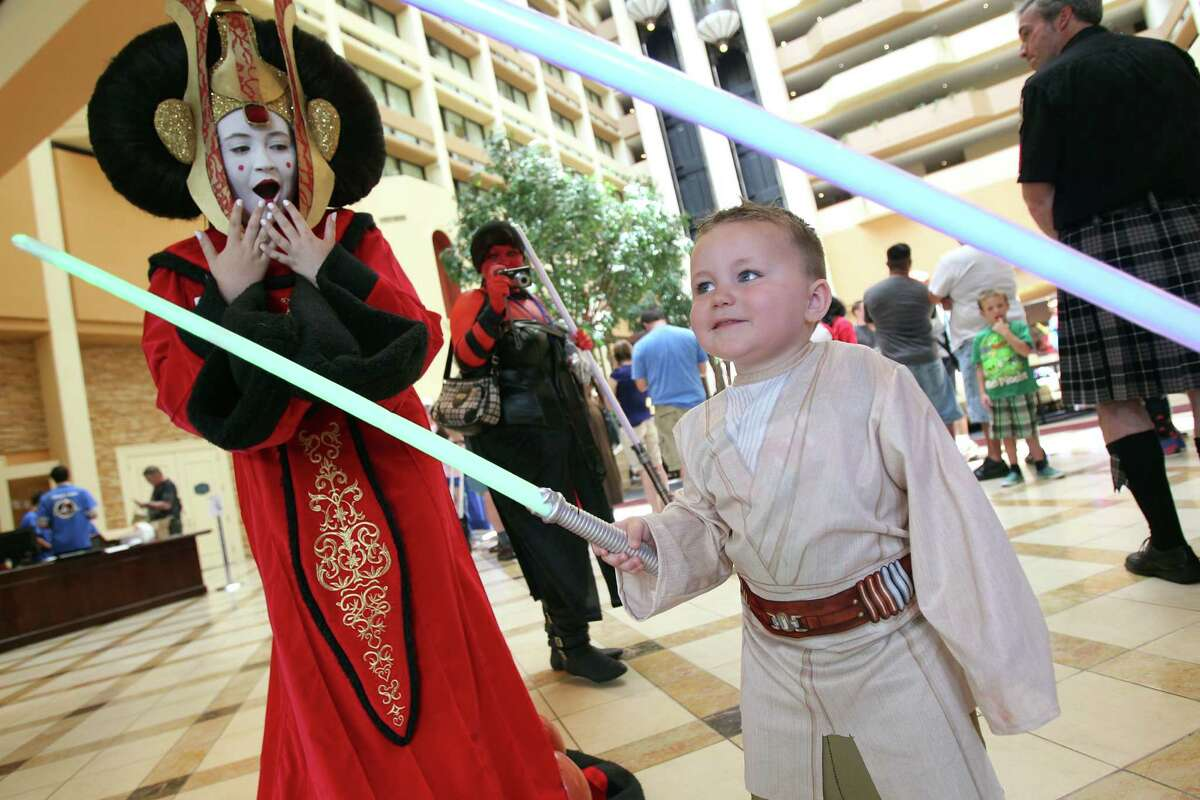 Payton Schmall, 15, dressed as Star Wars 'Queen Amidala', views Luke Jackson, 3, dressed as 'Luke Skywalker', as he battles with his lightsaber other characters during the Space City Con 2013 at the Marriott Westchase on Friday, Aug. 2, 2013, in Houston. The Space City Con 2013, a family friendly convention, kicks off today and ends Sunday.