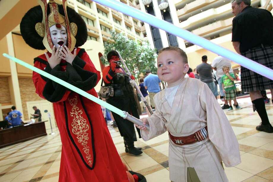 Payton Schmall, 15, dressed as Star Wars 'Queen Amidala', views Luke Jackson, 3, dressed as 'Luke Skywalker', as he battles with his lightsaber other characters during the Space City Con 2013 at the Marriott Westchase on Friday, Aug. 2, 2013, in Houston.  The Space City Con 2013, a family friendly convention, kicks off today and ends Sunday. Photo: Mayra Beltran, Houston Chronicle / © 2013 Houston Chronicle