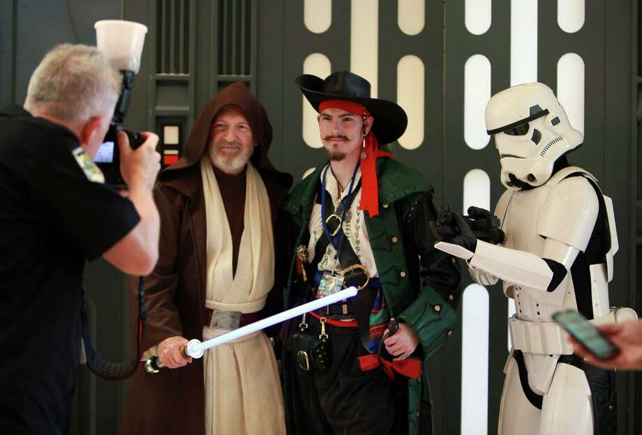 Robert Praetorius, Jr., center, dressed as Capt. Robert, is photographed with Star Wars characters during the start of  Space City Con 2013 at the Marriott Westchase on Friday, Aug. 2, 2013, in Houston.  The Space City Con 2013, a family friendly convention, kicks off today and ends Sunday. Photo: Mayra Beltran, Houston Chronicle / © 2013 Houston Chronicle