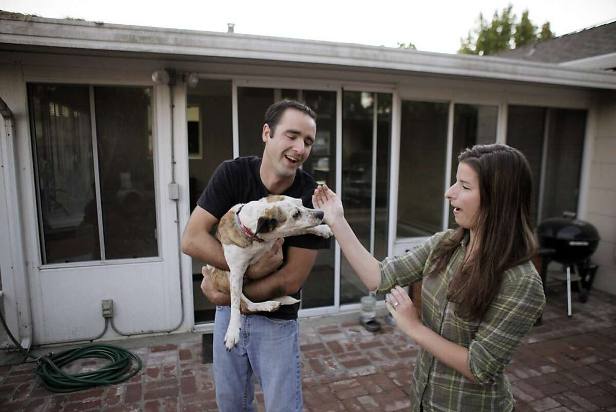 Nick Palmer and Teresa Lasaga with their dog Betty at their new home on Thursday, August 1, 2013, in San Mateo, Calif. Nick Palmer and Teresa Lasaga bought their first home in a pocket listing in San Mateo after putting in 16 offers.