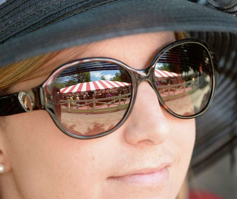 The unmistakable red and white awnings of the of Saratoga Race Course reflect in the glasses of Jennifer Nason Friday, Aug. 2, 2013, at Saratoga Race Course in Saratoga Springs, N.Y. (Skip Dickstein/Times Union) Photo: SKIP DICKSTEIN
