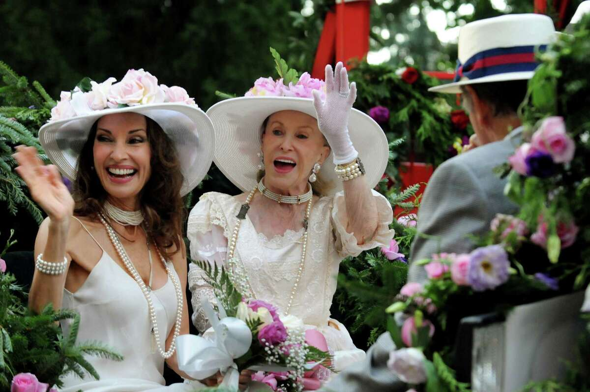 Marylou Whitney, center, and Susan Lucci, left, wave to their adoring fans during an Old Fashioned Floral Fete Promenade to celebrate 150 years of thoroughbred racing on Friday, Aug. 2, 2013, in Saratoga Springs, N.Y. (Cindy Schultz / Times Union)