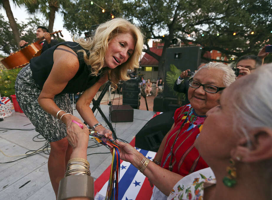 State Sen. Wendy Davis (left) accepts a fused-glass heart from Gloria Uribe (right) and Enedina Casarez Vasquez (center) during the inaugural Bexar County Democratic Party Family Reunion at Maverick Plaza in La Villita. Photo: Photos By Edward A. Ornelas / San Antonio Express-News
