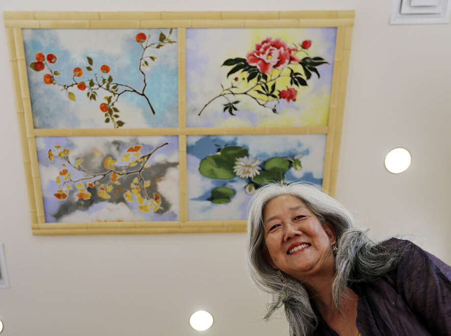 California artist Nancy Enkoji displays the panels she created, based on her late mother's childhood recollections. Photo: Edward A. Ornelas / San Antonio Express-News