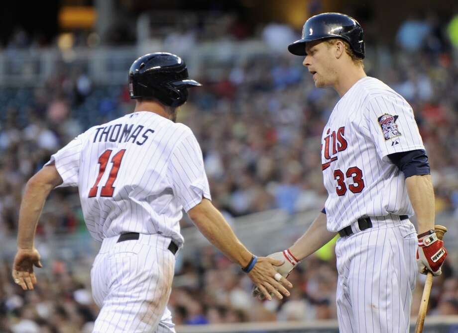 Justin Morneau congratulates teammate Clete Thomas after scoring a run. Photo: Hannah Foslien, Getty Images
