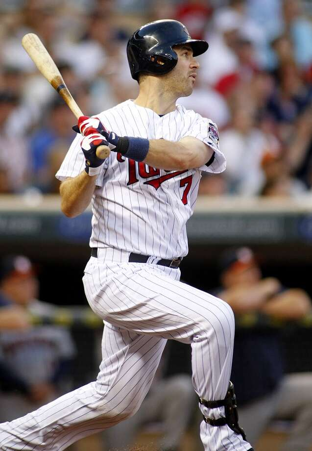 Joe Mauer follows through on a sacrifice fly scoring teammate Clete Thomas. Photo: ANDY CLAYTON-KING, Associated Press