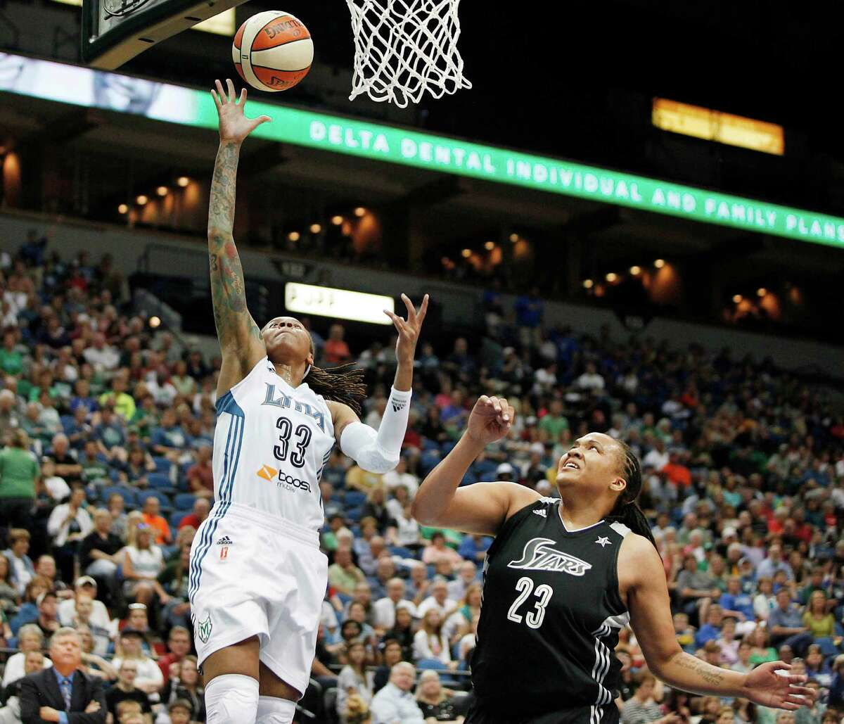 Minnesota Lynx guard Seimone Augustus (33) goes up to the basket past San Antonio Silver Stars forward Danielle Adams (23) during the first half of a WNBA basketball game, Friday, Aug. 2, 2013, in Minneapolis. (AP Photo/Stacy Bengs)