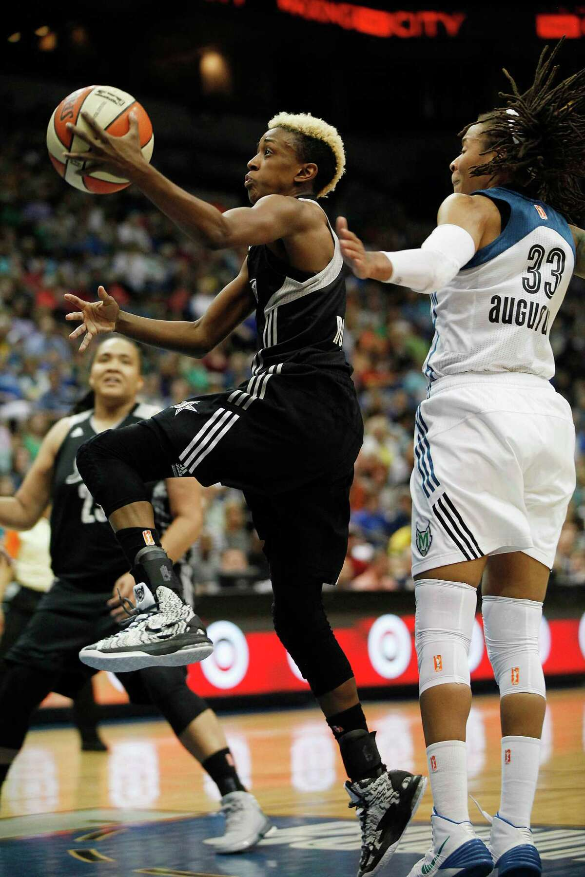 San Antonio Silver Stars guard Danielle Robinson, center, drives to the basket past Minnesota Lynx guard Seimone Augustus,right, in the second half of a WNBA basketball game, Friday, August 2, 2013, in Minneapolis. The Lynx won 85-63. (AP Photo/Stacy Bengs)