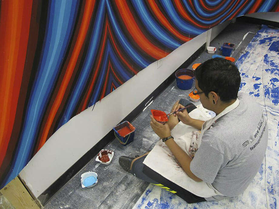 "Work proceeds on a mural by local artist Alex Rubio titled ""Vortex."" The mural is being created indoors on a flexible material called polytab fabric and will be moved to its outdoor location. It will be sprayed with an anti-graffiti coating. Photo: Courtesy Photo"