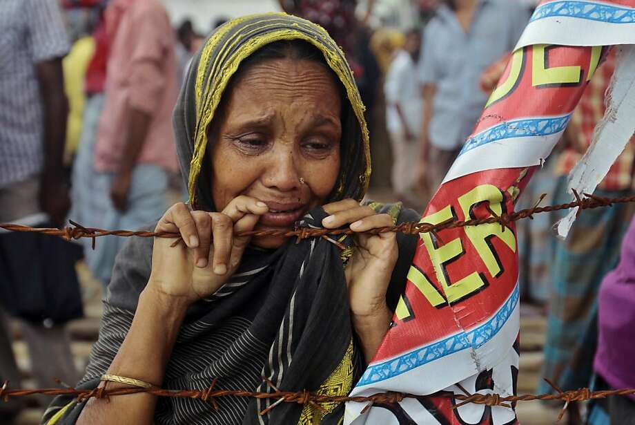 A Bangladeshi woman cries at the site of Rana Plaza building collapse, the worst tragedy in the history of the global garment industry, in Savar near Dhaka, Bangladesh, Friday, Aug. 2, 2013. The deadliest disaster in the history of the garment industry that killed 1,129 people with many missing, marks the 100th day on Friday.  (AP Photo/A.M. Ahad) Photo: A.M. Ahad, Associated Press